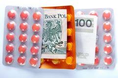 Dinero y píldoras Foto de archivo