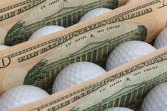 Dinero y pelotas de golf Fotografía de archivo