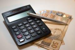 Dinero y pluma Imagenes de archivo