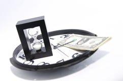 Dinero y reloj de arena en un reloj Fotos de archivo libres de regalías