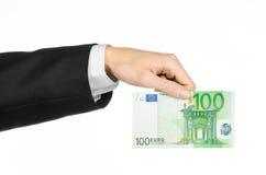 Dinero y tema del negocio: dé en un traje negro que lleva a cabo un euro del billete de banco 100 aislado en un fondo blanco en e Imagen de archivo libre de regalías