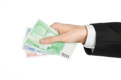 Dinero y tema del negocio: dé en un traje negro que sostiene los billetes de banco 10,20 y el euro 100 en fondo aislado blanco en Imagenes de archivo