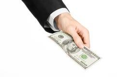 Dinero y tema del negocio: dé en un traje negro que sostiene un billete de banco de 100 dólares en fondo aislado blanco en estudi Imagen de archivo