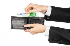Dinero y tema del negocio: dé en un traje negro que sostiene una cartera con 100 billetes de banco euro aislados en el fondo blan Imagenes de archivo