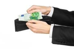 Dinero y tema del negocio: dé en un traje negro que sostiene una cartera con 100 billetes de banco euro aislados en el fondo blan Foto de archivo