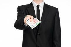 Dinero y tema del negocio: un hombre en un traje negro está sosteniendo el dinero euro aislado en el fondo blanco en estudio Imagen de archivo