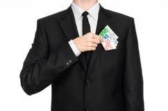 Dinero y tema del negocio: un hombre en un traje negro está sosteniendo el dinero euro aislado en el fondo blanco en estudio Fotos de archivo
