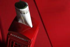 Dinero y una cabina de teléfono inglesa imagen de archivo