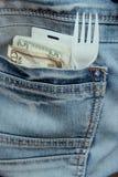 Dineros, llave de tarjeta y bifurcación en un bolsillo de los tejanos del empleado que se apresura en un primer de la hora de la  imágenes de archivo libres de regalías