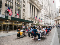 Diners at cafe tables on pedestrian area in front of New York St. New York, NY, June 16, 2015: Diners at cafe tables in front of New York Stock Exchange, Lower stock image