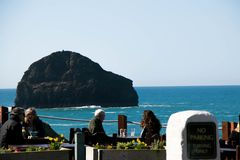 Diners enjoying lunch at an ocean view restaurant at Trebarwith Stand in Cornwall, England. Diners enjoy lunch from a restaurant with an ocean view over Stock Image