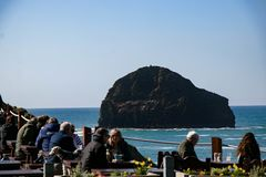 Diners enjoying lunch at an ocean view restaurant at Trebarwith Stand in Cornwall, England. Diners enjoy lunch from a restaurant with an ocean view over Stock Photography