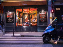 Diners lounge inside Le Chinon, a Paris bistrot. Male diners lounge inside the Paris bistrot Le Chinon. Scene shot from the street; motorscooter coming into view Royalty Free Stock Photo