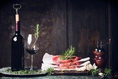 Dinervoorbereiding met ruw lapjes vlees, Fles en glas rode wijn, rozemarijn en zout en peperschudbekers op keukenlijst bij donker Stock Foto