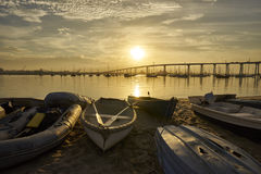 Dinghies on Coronado Island`s shore at sunrise. Coronado Island shore; San Diego and Coronado Bridge in background royalty free stock photos