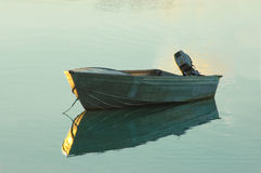 Dinghy anchored on a glassy sea at Sunrise stock image