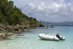 Dinghy anchored by shore. Inflatable dinghy anchored by rocky shore with boat in background royalty free stock photos