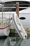 Dinghy Attached to Sailboat. An inflatable dinghy is attached to the transom of a sailboat providing better land accessibility Royalty Free Stock Photos