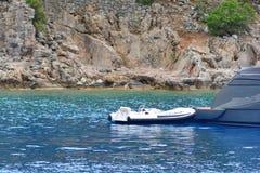 Dinghy boat near the luxury yacht.  stock photos