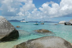 Dinghy coming into beach. Dinghy coming into a fine white sand beach with large granite boulders and turquoise waters.  The Baths.  British Virgin Islands Royalty Free Stock Image