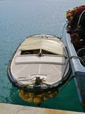 The dinghy by a fishing trawler Stock Photography