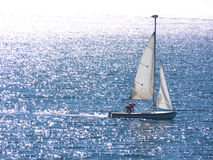 Dinghy sailing on silvery sea. A dingy with single sailor sailing on beautiful blue waters of the Pacific at Santa Cruz California. Sun reflecting on waves and Royalty Free Stock Image