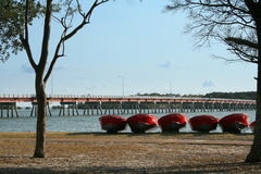 Dinghys for Hire. A row of red dinghy boats for hire on Bribie Island with the bridge in the background Royalty Free Stock Photos