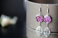 Dingla örhängen som göras av epoxykåda och torkade rosa kronblad arkivfoto