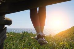 Dingla fot i skor, kvinnasammanträde på stranden royaltyfri foto
