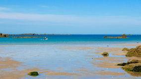With the dingy alone. One man in a dingy taking off towards the horizon. Tropical colored water, Sandy beach and small rocky islands. Archipelago of Iles de Stock Images