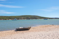 Dingy on the Beach. Dingy on the sandy beach with the Murchison River landscape with boats and coastal dunes in the background under a blue sky in Kalbarri Royalty Free Stock Image