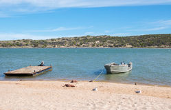 Dingy and Pontoon Boat. Floating in the Murchison River with vegetated coastal dunes under a blue sky in Kalbarri, Western Australia stock image