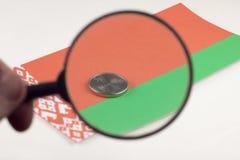 Dinheiro Belorussian com lupa, o rublo bielorrusso da bandeira foto de stock