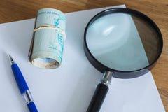 Dinheiro brasileiro, reais, altamente nominais com uma folha de papel e uma pena para cálculos Fotos de Stock Royalty Free