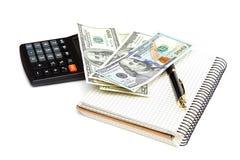 Dinheiro, calculadora, bloco de notas e pena em um fundo branco Foto de Stock Royalty Free