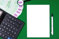 Dinheiro, calculadora e caderno no fundo verde imagens de stock