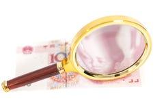 dinheiro chinês de 100 yuan com vidro da lente de aumento Imagens de Stock