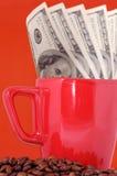 Dinheiro, copo e grãos de café Imagens de Stock