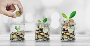 Dinheiro da economia, conceitos da operação bancária e do investimento, mão que põe a moeda nas garrafas de vidro com incandescên fotografia de stock