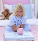 Dinheiro da economia da menina em um banco piggy Fotografia de Stock Royalty Free