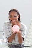 Dinheiro da economia da mulher de negócios em um piggybank Fotografia de Stock
