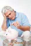 Dinheiro da economia do homem sênior em piggy Foto de Stock