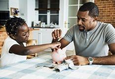 Dinheiro da economia do paizinho e da filha ao mealheiro foto de stock