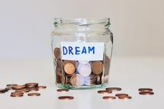 Dinheiro da economia para o conceito ideal Frasco de vidro completamente das moedas e do sonho do sinal imagem de stock
