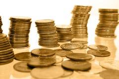 Dinheiro da moeda nas pilhas de tons do ouro Imagem de Stock