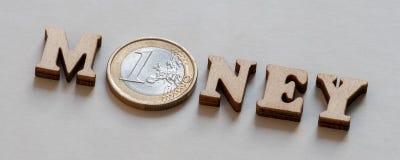 DINHEIRO da palavra de letras de madeira e de um euro em um fundo cinzento Conceito monetário de investimentos financeiros ou de  foto de stock