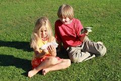 Dinheiro da terra arrendada do rapaz pequeno e da menina Fotografia de Stock