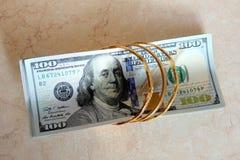 Dinheiro das notas de dólar com ouro Fotografia de Stock Royalty Free