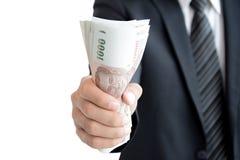 Dinheiro de agarramento da mão do homem de negócios, baht tailandês (THB) Foto de Stock Royalty Free