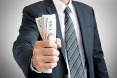 Dinheiro de agarramento da mão do homem de negócios, baht tailandês (THB) Fotos de Stock